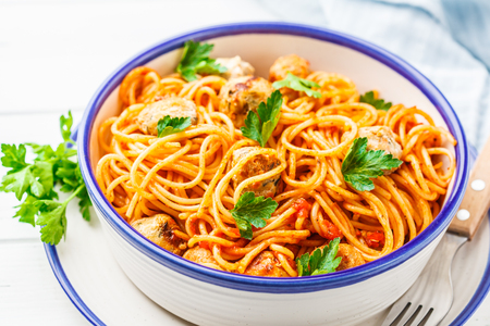 Pasta with turkey meatballs and tomato sauce in a white dish.