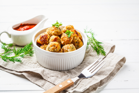 Healthy chicken meatballs with greens and tomato sauce on a white background.