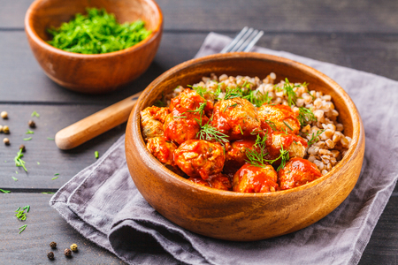Chicken meatballs in tomato sauce with buckwheat in a wooden bowl on a dark wooden background.
