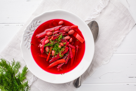 Vegetarian beet soup (borscht) with beans and vegetables in a white plate on a white wooden background.