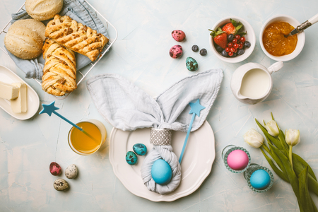 Easter Breakfast table. Blue background, festive table setting, top view. Stock Photo
