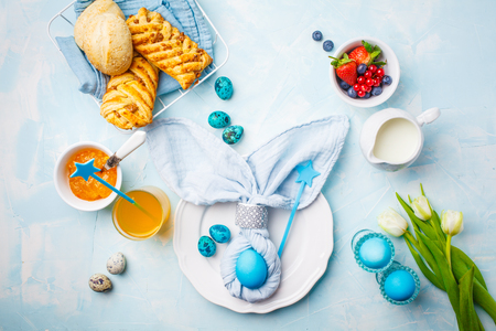 Easter Breakfast table. Blue background, festive table setting, top view. Stockfoto