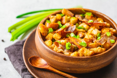 Spanish migas with pork and green onions in wooden bowl on a white background.