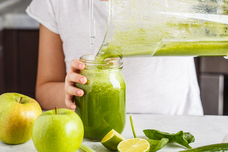 Preparation of green smoothie in the kitchen. Child cooking spinach apple cucumber smoothie. Healthy plant based food.