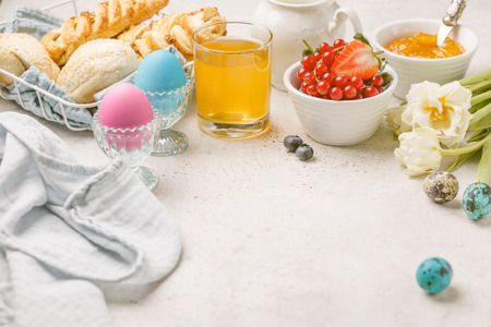 Easter Breakfast table. Colored eggs, milk, juice and jam, white background. Food frame. Stockfoto