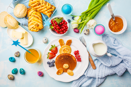 Easter bunny of pancakes with berries. Easter Breakfast table. Colored eggs, milk, juice and jam. Blue background, top view.