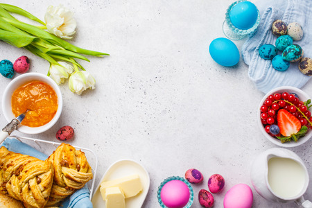 Easter Breakfast table. Colored eggs, flowers, milk, juice and jam, white background. Top view, food frame, easter concept, copy space.