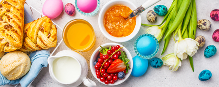 Easter Breakfast table. Colored eggs, flowers, milk, juice and jam, white background. Top view, easter concept, copy space.