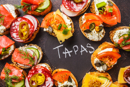 Assorted spanish tapas with fish, sausage, cheese and vegetables. Dark background, flat lay.