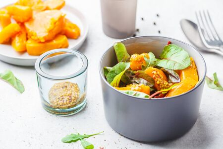 Green salad with pumpkin and mustard in a gray bowl. Healthy vegan food concept.