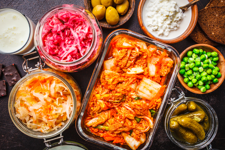 Probiotics food background. Kimchi, beet sauerkraut, sauerkraut, cottage cheese, olives, bread, chocolate, kefir and pickled cucumbers in glass jars, dark background, top view.