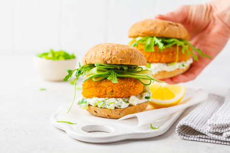 Fish burger with cucumber, arugula and mayonnaise sauce, white background, vegetarian food. Banco de Imagens