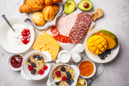 Continental breakfast table with croissants, jam, ham, butter, granola and fruit. Top view, food background.