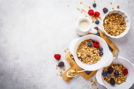 Breakfast food background. Granola with milk and berries on a white table, top view, copy space.