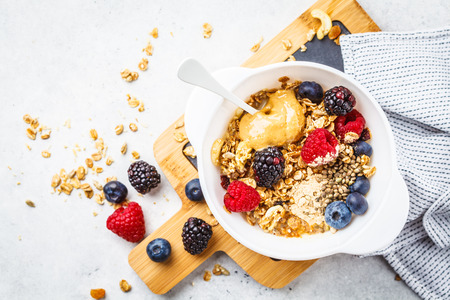 Breakfast food background. Granola with hemp seeds, maca powder, peanut butter and berries on a white table.