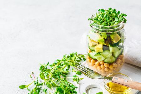 Grüner Salat mit Kichererbsen in einem Glas, weißer Hintergrund, Kopienraum. Detox, veganes Essen, pflanzliches Ernährungskonzept.