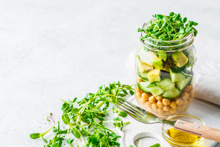 Green salad with chickpeas in a jar, white background, copy space. Detox, vegan food, plant based diet concept.