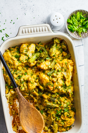Broccoli, green peas and cauliflower cheese casserole in the oven dish. Vegan vegetable casserole with nutritional yeast. Reklamní fotografie