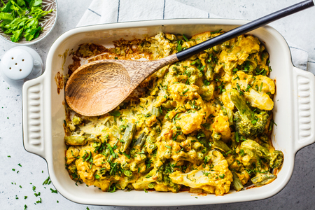 Broccoli, green peas and cauliflower cheese casserole in the oven dish. Vegan vegetable casserole with nutritional yeast.