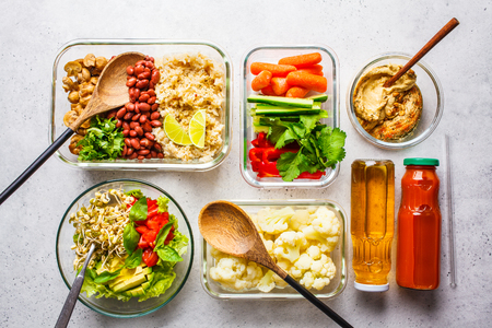 Healthy vegan food in glass containers, top view. Rice, beans, vegetables, hummus and juice for take-away lunch Reklamní fotografie