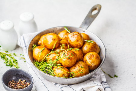 Baked potatoes in a cast iron skillet, white background. Banco de Imagens