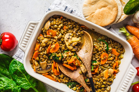 Vegan lentil curry with vegetables, top view. Healthy vegetarian food background. Imagens