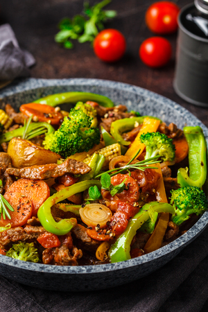 Fried beef stroganoff with potatoes, broccoli, corn, pepper, carrots and sauce in a pan, dark background. Banco de Imagens