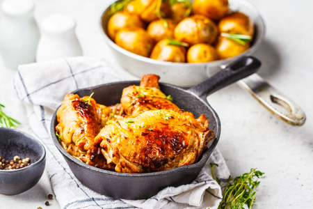 Grilled chicken and baked potatoes in a cast iron skillet.