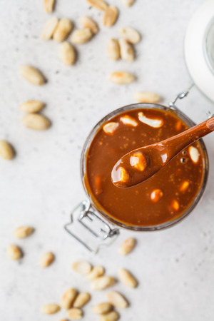 Homemade salted caramel with nuts in a glass jar, top view. Ingredient for cake snickers. Imagens