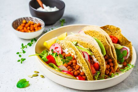 Vegan tacos with baked chickpeas, avocado, sauce and vegetables on a white background.