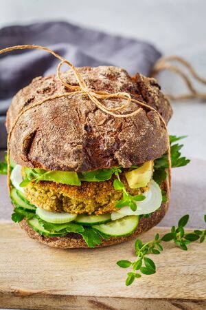 Vegan sandwich with chickpea cutlet, avocado, cucumber and greens in rye bread.