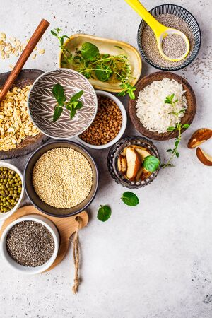 Flat lay of superfoods and cereals selection in bowls - rice, chia seeds, nuts, oatmeal, buckwheat, quinoa, mung beans and greens on a white background.