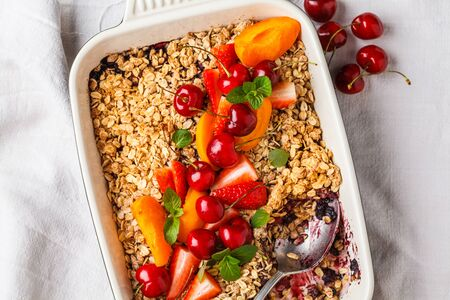 Fruits and berries oat crumble in oven dish on a gray background.