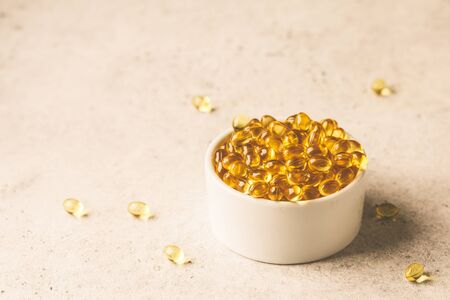 Fish oil capsules (omega 3) in a white bowl on a gray background, copy space.