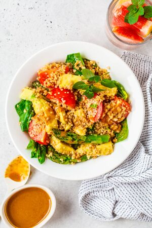 Green salad with quinoa, avocado and asparagus in a white bowl. Vegan food concept.