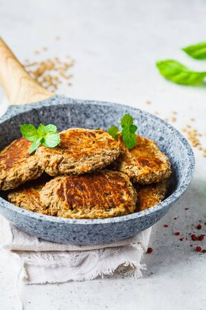 Lentil cutlets in a gray frying pan. Healthy vegan food concept.