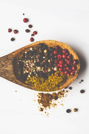 Various peppers and spices on a wooden spoon, white background.