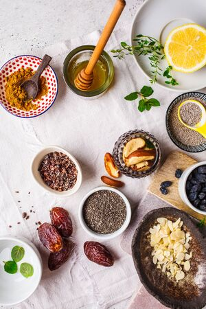 Flt lay of super foods - honey, dates, turmeric, lemon, nuts and chia on white background. Cooking healthy drink concept.