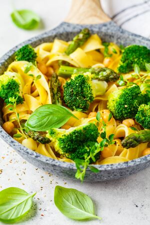 Vegetarian pasta with broccoli, asparagus and chickpeas in a pan. Vegan food concept.