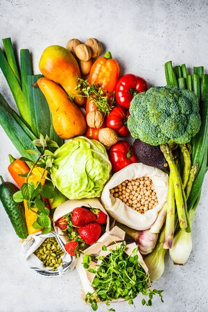 Balanced vegetarian food background. Vegetables, fruits, nuts, sprouts, seeds, chickpeas on a white background, top view.
