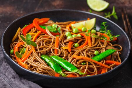 Vegan buckwheat soba noodles with vegetables in a black plate on a dark background.