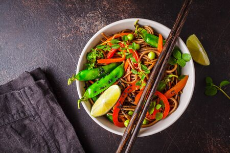 Vegan buckwheat soba noodles with vegetables on a dark background.