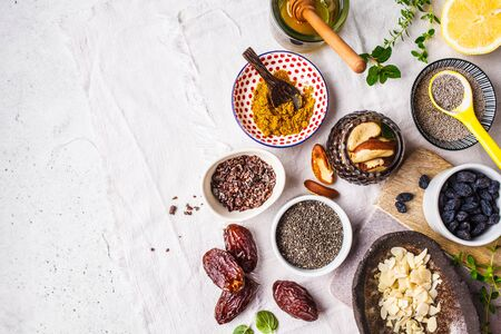 Flt lay of super foods - honey, dates, turmeric, lemon, nuts and chia on a white background. Cooking healthy food concept.