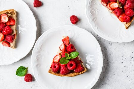 Flat lay of berry tart with raspberries, strawberries and cream on a white plate. Stok Fotoğraf