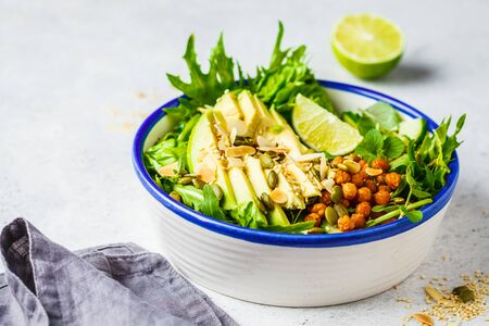Green healthy salad with avocado, baked chickpeas and seeds in a white bowl. Stok Fotoğraf