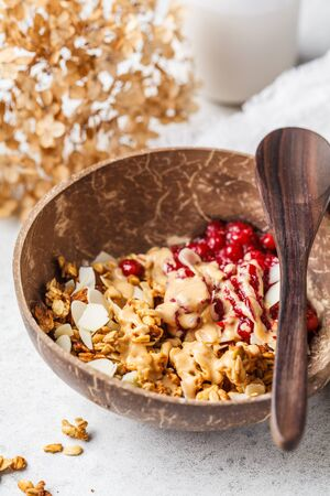 Homemade granola with cranberries and peanut butter in a coconut bowl. Healthy vegan food concept.