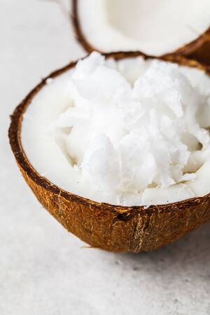 Coconut oil in a coconut shell on gray background.