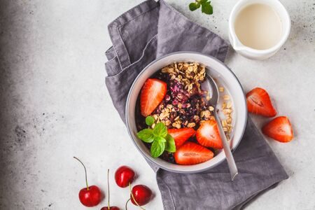 Baked oatmeal with berries and milk in a gray bowl. Vegan breakfast.