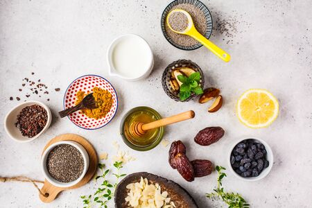 Flt lay of super foods - honey, dates, milk, turmeric, lemon, nuts and chia on a white background. Cooking healthy food concept.