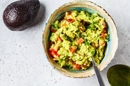 Fresh avocado tomato guacamole in a bowl, top view. Healthy vegan food concept. Reklamní fotografie